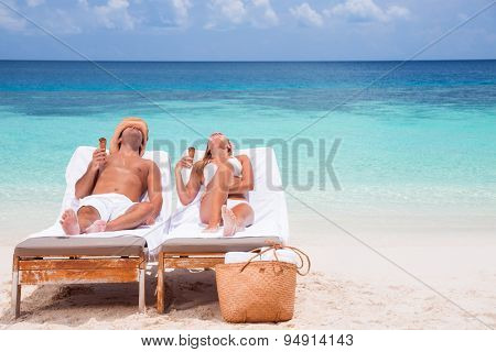 Happy couple on beach resort, tanning on sunbed and eating tasty sweet ice cream, enjoying summer time on beautiful sandy coast