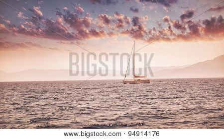 Beautiful sea landscape, sailboat sailing in the distance in mild pink sunset light, romantic vacation in the sea, beauty of summer nature