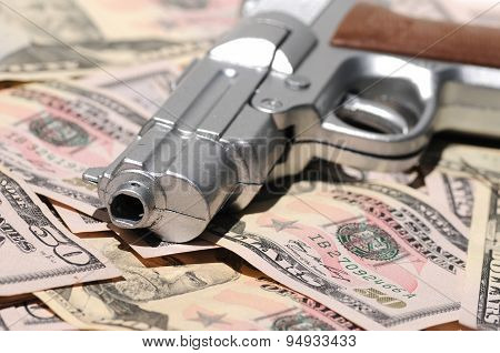 Money Crime Scene: A Gun's Muzzle On Banknotes Of Us Dollars