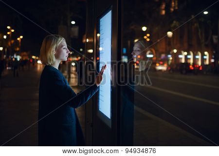 Young woman using modern urban application of bus stop in Barcelona find out schedule of transport