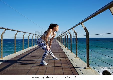 Sporty woman stretching legs while standing on wooden jetty with ocean horizon on background