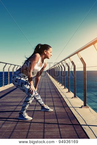 Healthy woman stretching before her run while standing on wooden jetty with beautiful sea horizon
