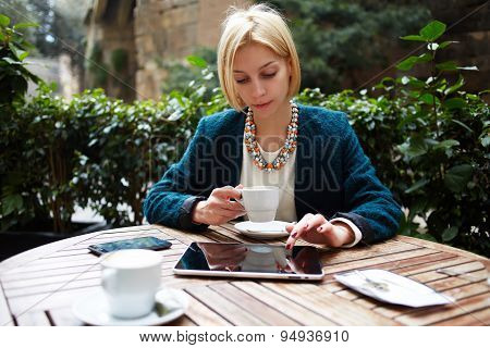 Attractive caucasian blond well dressed woman using touchpad while sitting in coffee shop
