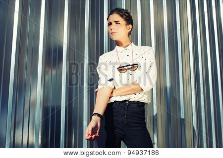Young fashionable model standing on silver wall background while looking away