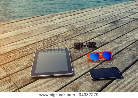 Presentation with blank screen digital tablet smart phone and couple of sunglases