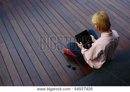 Freelancer girl working on her digital tablet with big copy space while sitting on a wooden floor
