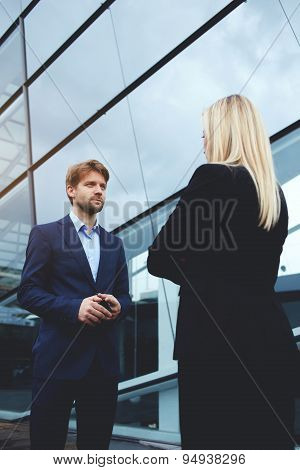 Rear view managing businesswoman with crossed arms standing opposite smiling employee