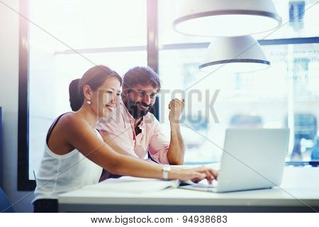 Two business people discussing ideas in co-working space with a laptop or notebook in front of them