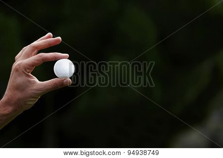 Male hand holding a golf ball on green nature background with big copy space for your text message