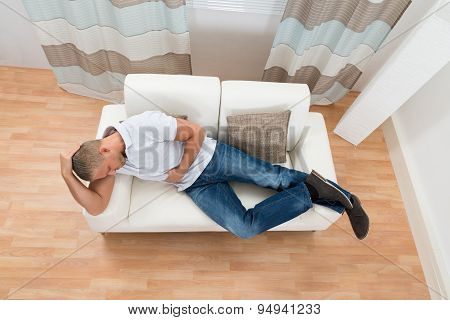Young Man On Sofa Suffering From Stomach Pain poster