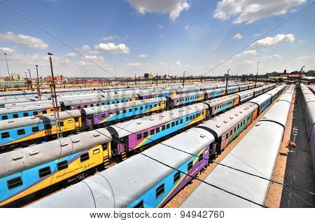 Johannesburg South Africa - March 26 2012: The Braamfontein Railway Yards with their colorful cars under the Nelson Mandela Bridge. The yards lie between Newtown and Braamfontein. poster