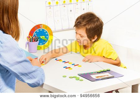 Concentrated boy putting colorful coins in order during developing game with his mother sitting at the table indoors poster