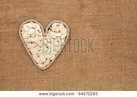 Heart Made From Rope With Pumpkin Seeds Lying On Sackcloth