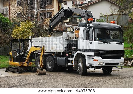 A compact mini hydraulic excavator with a rotating house platform and a truck-mounted swing-arm crane. poster