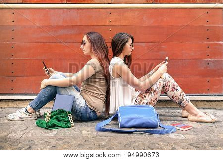 Hipster Couple Of Girlfriends In Disinterest Moment With Mobile Smart Phones - Relationship Concept