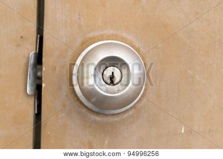 Old And Dirty Doorknob On Brown Wooden Door