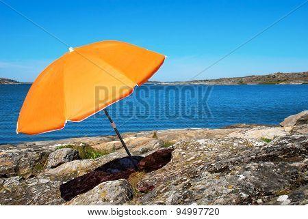 Swedish Coast With Blue Sea And Orange Parasol