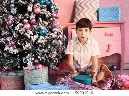 preteen handsome boy with christmas tree and presents