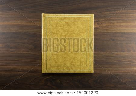 Gold or beige photo album or Year book cover, blank, placed on a dark colored wooden table.