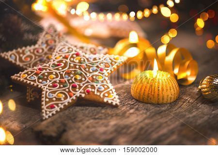 Christmas gingerbread cookies on wooden table decorated with garland and candles. Traditional Christmas food on old shabby wood, vintage styled backdrop