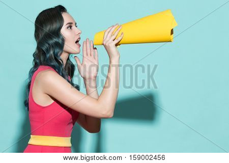 Young beautiful girl speaks in a paper loudspeaker on a blue background.
