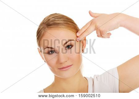 Young woman committing suicide with finger gun gesture.