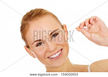 Young happy woman cleans her ear.