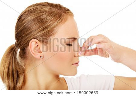 Young woman holding her nose because of a bad smell.