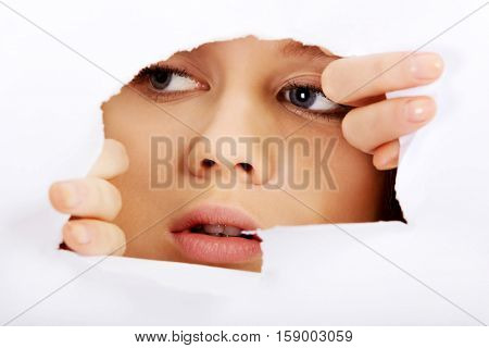 Teenage woman peeping through hole on paper.