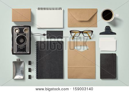 modern hipster style stationery mockup with various paper items, office supplies, glasses, coffee mug and vintage camera