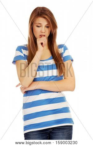 Worried teenage woman with folded arms biting nails
