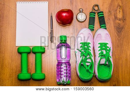Workout and fitness dieting copy space diary. Healthy lifestyle concept. Dumbbell, expander, water, hand and ball on rustic wooden table.