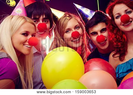 friends with red clown noses and balloons in club