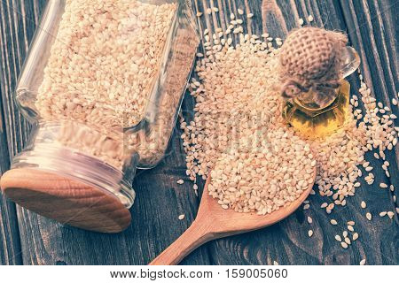 Sesame oil in bottle sesame seeds in jar spoon on wooden background. Top view