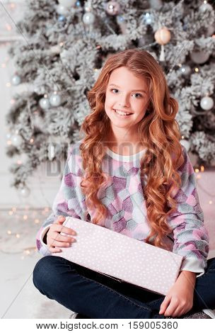 Happy teen girl 10-14 year old sitting with Christmas present in room. Looking at camera. Childhood. Wearing casual clothes. Childhood.