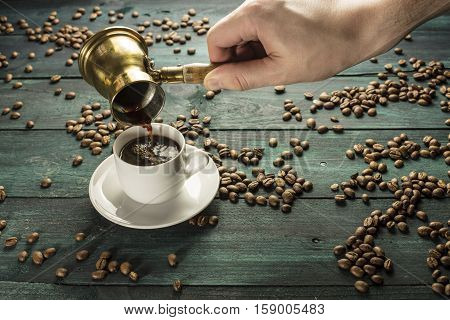 Strong coffee being poured from a vintage coffee pot into a white porcelain cup, on a dark background with scattered coffee beans and copyspace