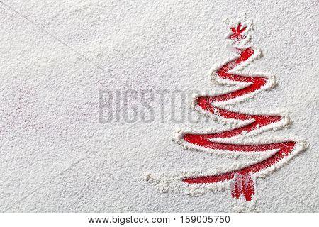 Christmas tree on flour background. White flour looks like snow. Top view