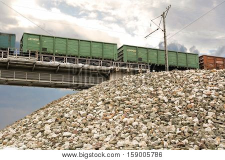 Freight train on the railway bridge. Green railcars on sky background.