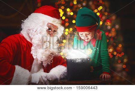 Santa Claus and helper child elf with bright magical gift in Christmas night