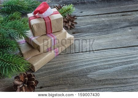 Christmas composition of pine cones spruce branches and stack of gift boxes with Santa's cap on the background of old unpainted wooden boards; with copy-space