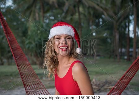 Young happy woman in santa hat and red swimsuit showing her tongue while sitting on the hammock on the sandy beach. Christmas beach vacation travel woman enjoying christmas on tropical beach