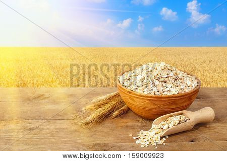 Oat flakes in bowl. Ears of oats and oatmeal in bowl on table with field with sunshine on the background. Agriculture and harvest concept. Gold field and blue sky. Uncooked porridge