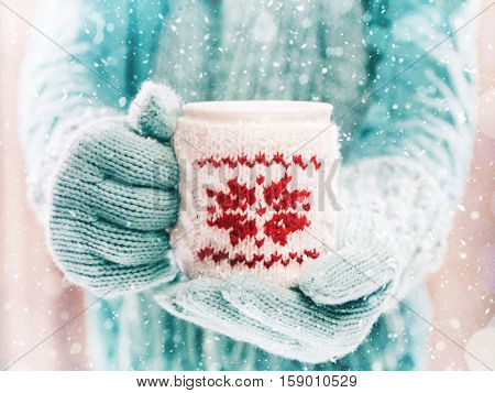 Woman holding winter cup close up on light background with snowfall. Woman hands in teal gloves holding a cozy mug with hot cocoa, tea or coffee. Winter and Christmas time concept.