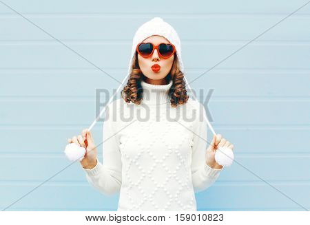 Happy Young Woman Blowing Red Lips Makes Air Kiss Wearing A Heart Shape Sunglasses, Knitted Hat, Swe