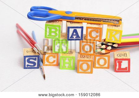 Back to school spelled with alphabet blocks displayed with coloring pencils paintbrushes and a scissor on a white background