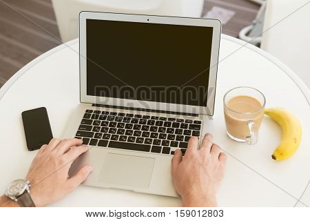 Typing on laptop in bright high-tech green office, coffee mug, bannana