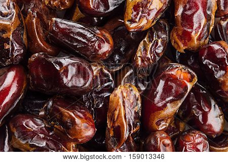 Date fruit closeup background. Heap of dried shiny brown red date fruit. Top view.