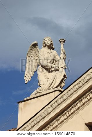 Angel statue with candelabra on top of Saint Rocco church in Rome Italy