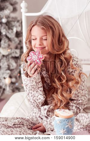 Smiling teen girl 12-14 year old eating gingerbread with cup of tea in room. Christmas tree. Holiday time. Childhood.