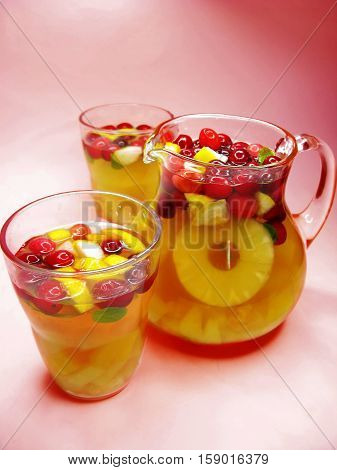 fruit cruchon cocktail punch in jug and two glasses with ice and fruit